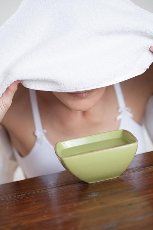 Frau mit Handtuch über dem Kopf inhaliert Wasserdampf über einer Schüssel.